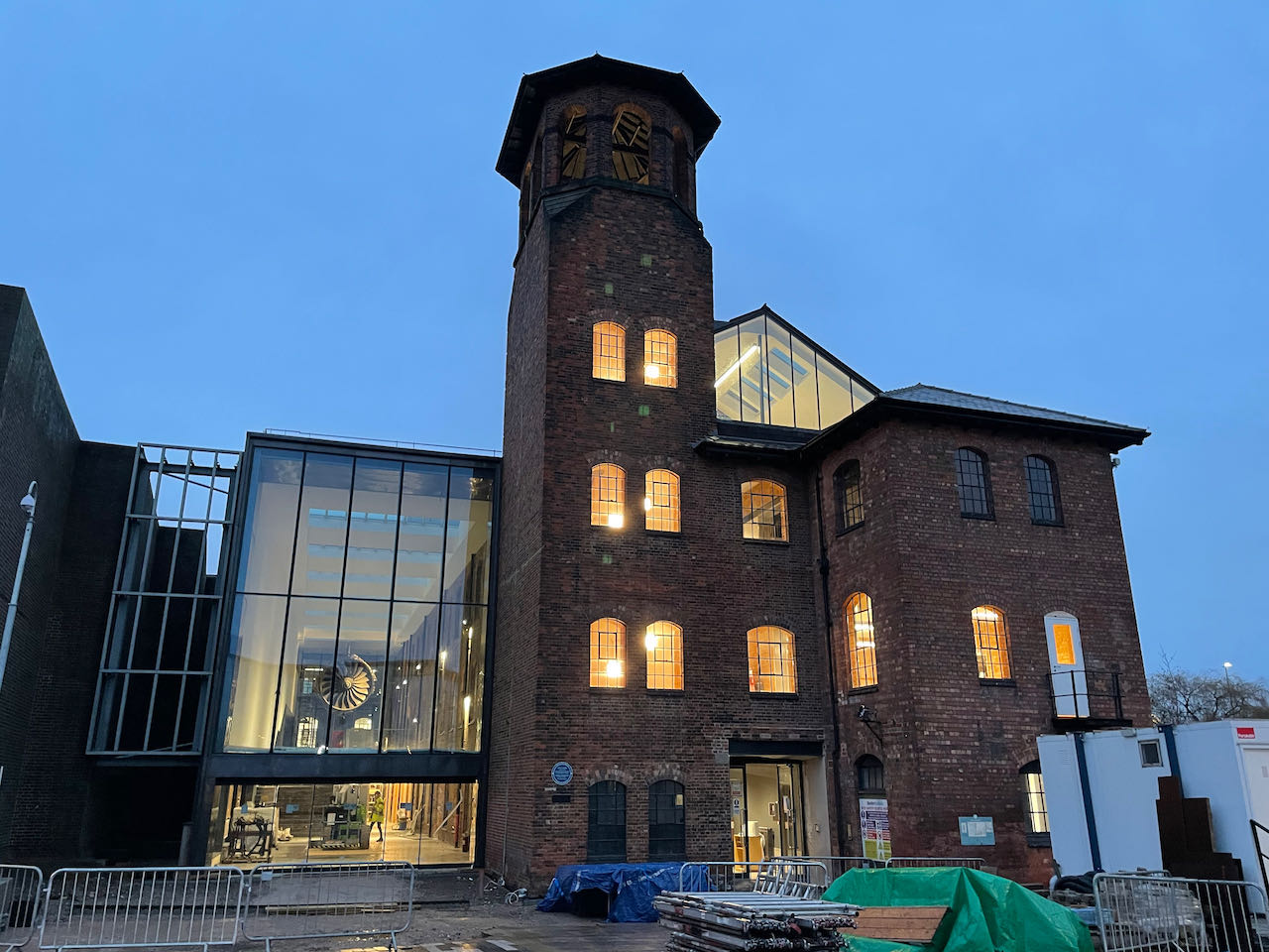The frontage of the Silk Mill at twilight with the interior lights illuminating the building