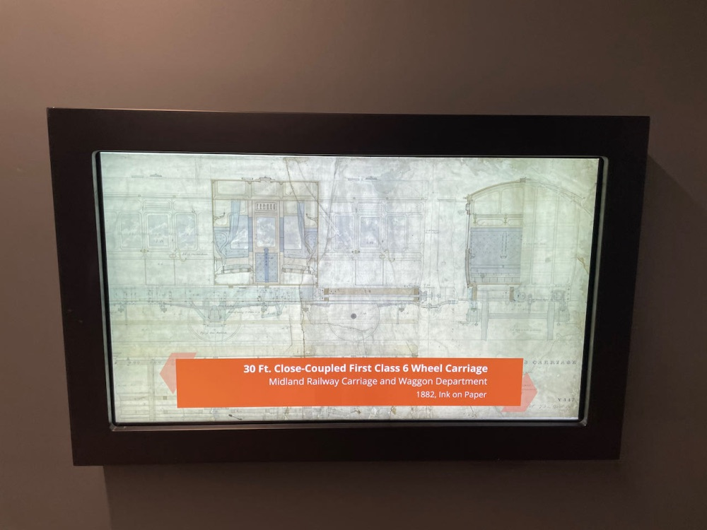 A display screen with a digital copy of a Midland Railway carriage drawing and the caption 30ft close coupled first class six wheel carriage