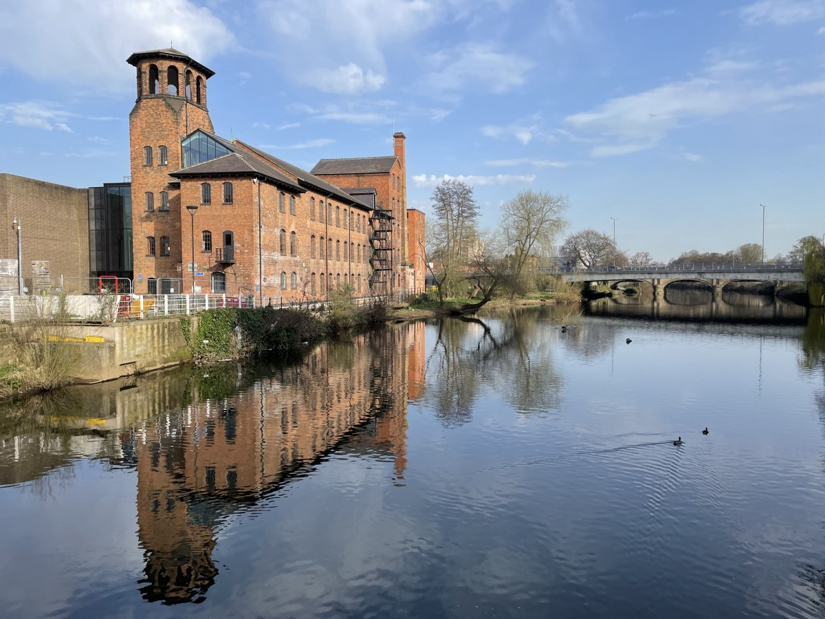 Derby's Silk Mill on a sunny day reflected in the river.
