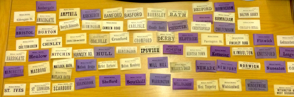 A collection of about two dozen rectangular luggage labels with the names of a wide variety of station names. Many are coloured purple, others are cream.